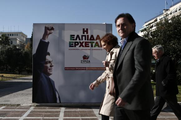 People walk past a banner with an image of Tsipras at the party's pre-election kiosk in Athens