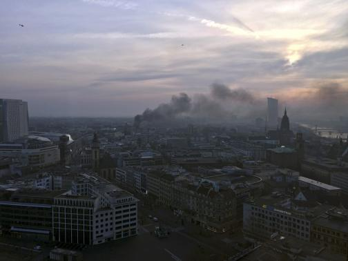 Smoke engulfs the city skyline during a protest of members of 'Blockupy' anti-capitalist movement near the ECB building before the official opening of its new headquarters in Frankfurt