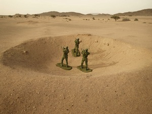 Polisario Soldiers stand posed as toy soldiers in a bomb crater from the conflict