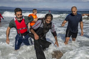 Gabriel Green Volunteers take a possible smuggler to shore on Lesvos, Greece Saturday afternoon after the man was rescued by two Spanish lifeguards as he attempted to float back to Turkey on a partially deflated raft after delivering a group of refugees. He was later delivered by volunteers from Drop in the Ocean to a police station in Molyvos.