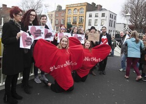 "20/1/2017. Donald Trump banners.  (L to R) (wearing hearts) Maria Schaler and Siona Cahil from Union Students of Ireland with protesters at the Hapenny Bridge in Dublin. Today Donald Trump's Presidential inauguration was marked by the dropping of a banner from the Ha'penny bridge which reads ""BRIDGES NOT WALLS – Love Trumps Hate. The events is one of scores of similar events across 3 continents in solidarity with people in the US who are likely to be the targets of the hate which has become associated with the Trump campaign.The action is coordinated by the European Network Against Racism Ireland (ENAR Ireland) and is supported by the Immigrant Council of Ireland, The Union of Students in Ireland (USI), the Migrant Rights Centre Ireland (MRCI) and other ENAR Ireland network members. Photo:Leah Farrell/RollingNews.ie"